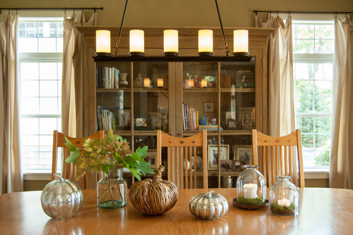 Dining room table centerpieces with candles and pumpkins